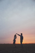a couple dancing under the sunset
