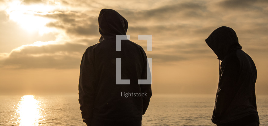 standing with backs to the camera on a beach at sunset