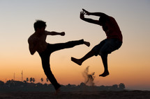 Silhouette of boys engaging in martial arts moves outside at dusk.
