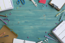 border of office supplies on turquoise wood background