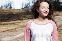 Smiling girl standing outside by a dirt road.