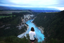 a woman at the top of a cliff looking down at a river