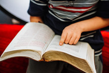 A young boy reads an open Bible while pointing to the words with his pointer finger.