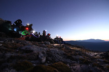 hikers with headlamps sitting on a mountainside