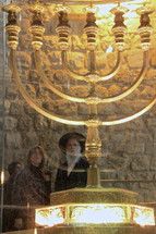 Observers viewing a seven-lamp Menorah at the Western Wall.