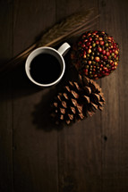 Cup of coffee sitting on wooden planks with pine cone, wheat stalk, and ball of berries.