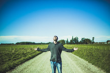 man standing in the middle of a dirt road with his hands raised