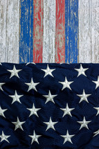 red, white, and blue stripes on weathered wood and stars of the American flag
