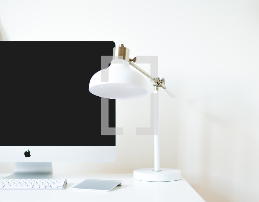 a desk with computer and lamp