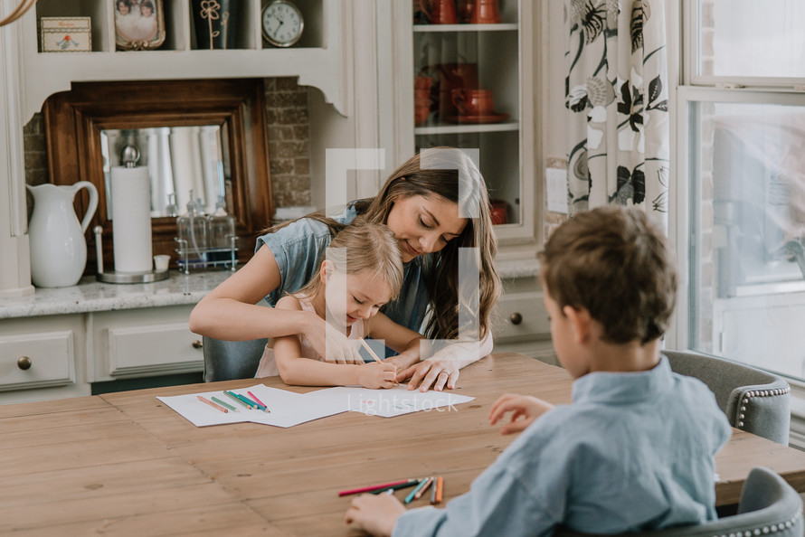 a mother coloring with her daughter and son