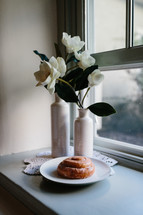 cinnamon bun on a plate by a window