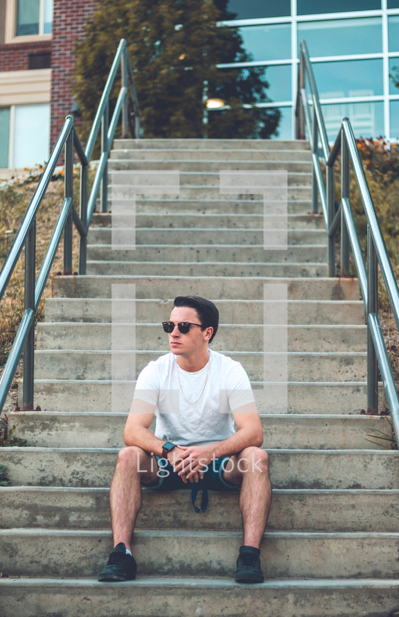 young man sitting on concrete steps at school