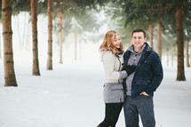 happy couple standing in snow