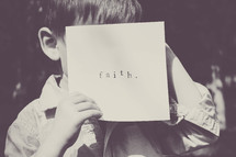 little boy hiding his face behind a piece of paper with the word faith