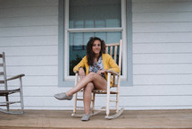 a teen on a front porch sitting in a rocking chair
