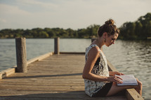Girl sitting on a wooden pier at a lake reading the Bible.