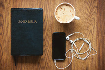 Santa Biblia, earbuds, iPhone, and cappuccino