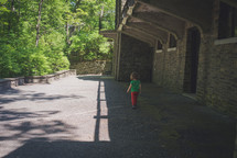 toddler girl walking outdoors near an old stone old