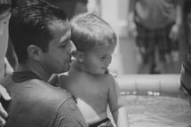 A man holds a little boy next to a baptismal pool.
