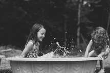 Two little girls playing in a plastic swimming pool.