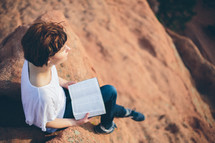 Woman sitting outside reading the Bible.