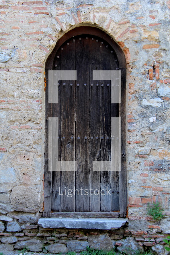 A wooden door in a stone wall.