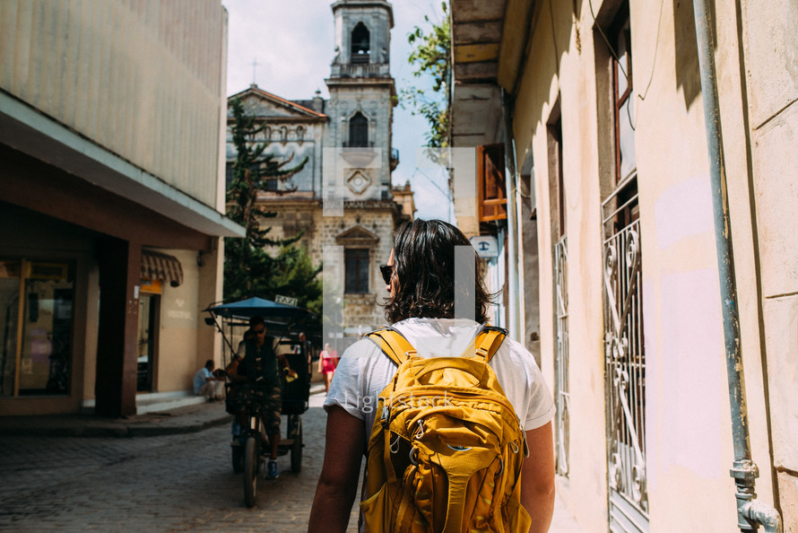 a man with a backpack walking on the narrow streets of Rome
