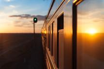 Train traveling through a desert land at sunrise.