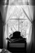 cowboy hat on a Bible in front of a window