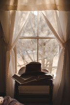 cowboy hat on a Bible in a window