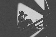 silhouette of a teen girl on a staircase holding a camera