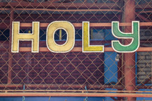 word Holy on a chain link fence