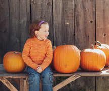 a child sitting with pumpkins