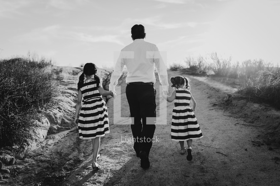 a father holding hands with his daughters as they walk up a sand dune
