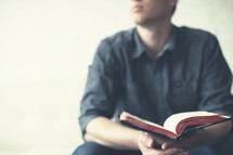 Man sitting on a sofa looking away with a Bible in hand.