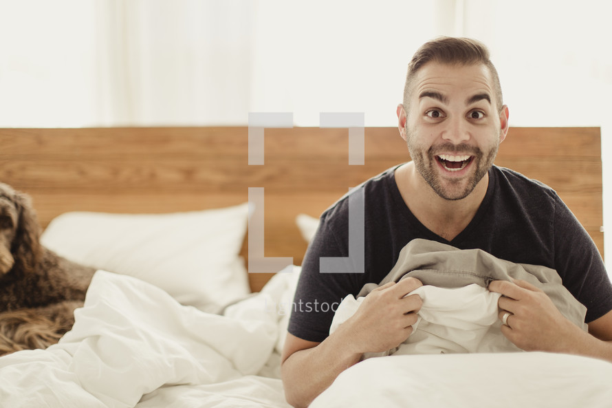 Happy man sitting up in bed with dog.