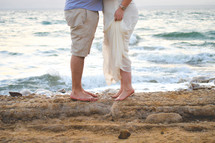 man and woman kissing on a beach