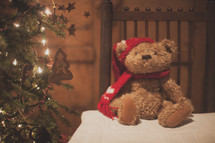 a holiday bear on a table and Christmas tree
