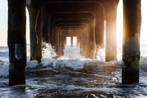 waves crashing under a pier