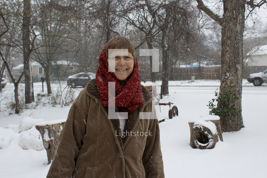 a woman in a scarf standing outdoors in the snow