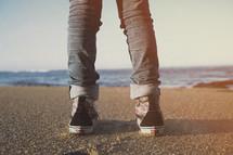 Person standing on a beach facing forward toward beach