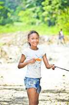 girl child holding a leash and eating a popsicle