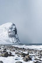 snow on rocks along a shore