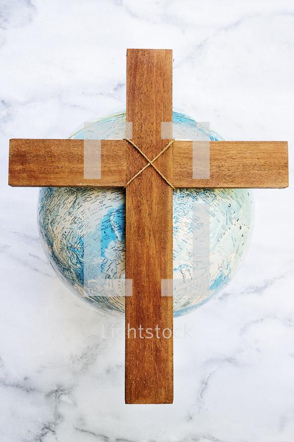 a wooden cross on a globe