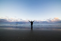 Man on a beach with arms raised toward sky.
