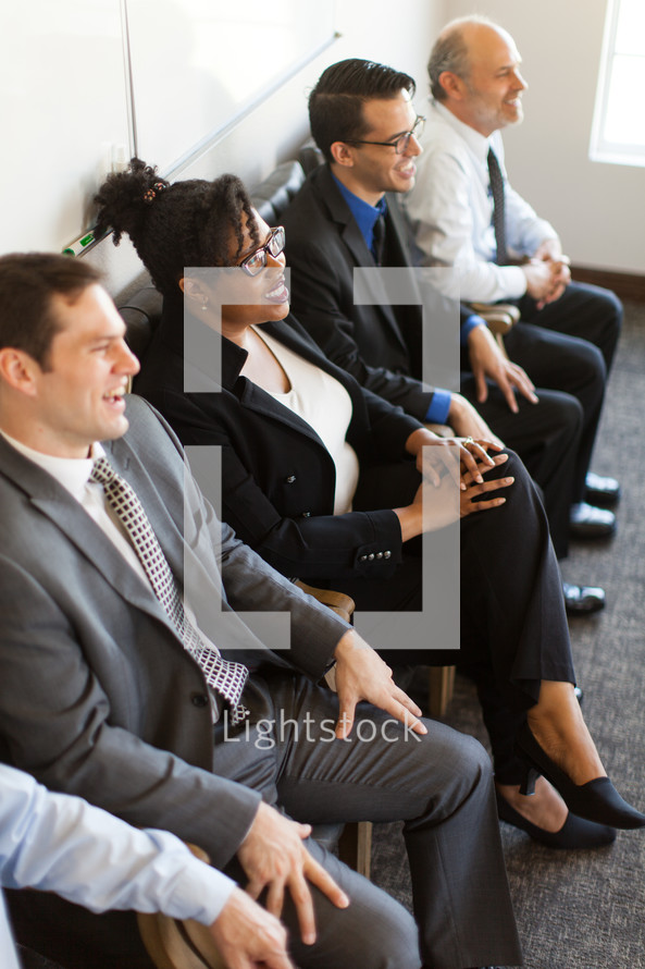 businesswomen and businessmen listening to a business meeting