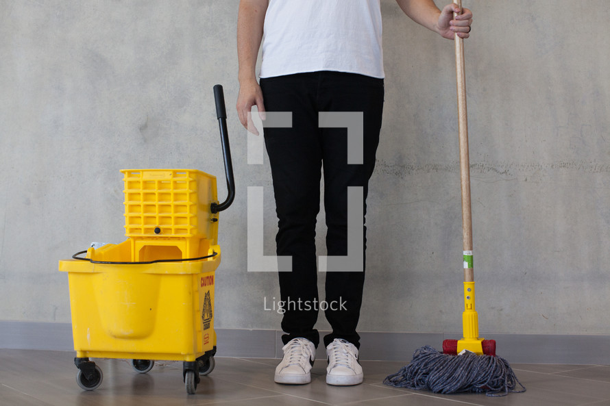 a man with a mop and mop bucket