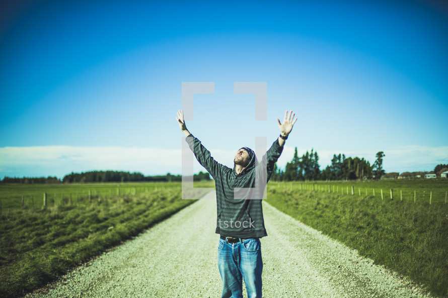 man standing in the middle of a dirt road with hands raised to God