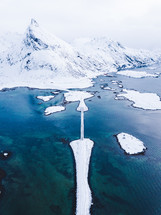 aerial view over a bridge leading to a snow covered island