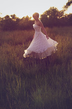 Woman in white dress twirling in a field of tall grass.